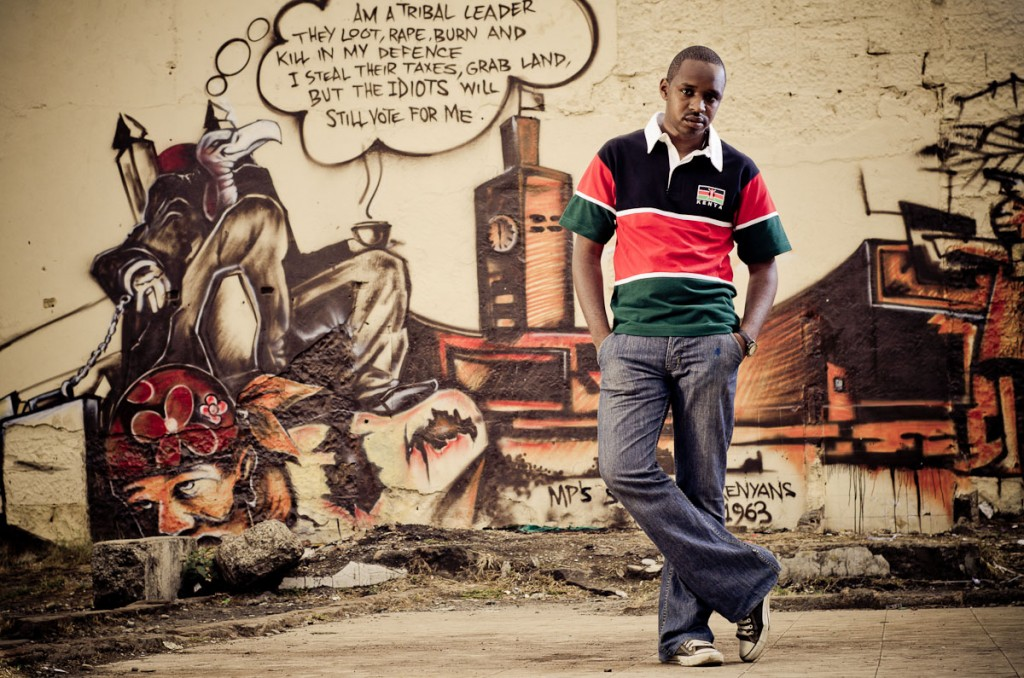 Boniface Mwangi poses in front of a graffiti mural. The activist has ignited a debate about who qualifies as a patriot. (Photo/ https://mpasho.co.ke)