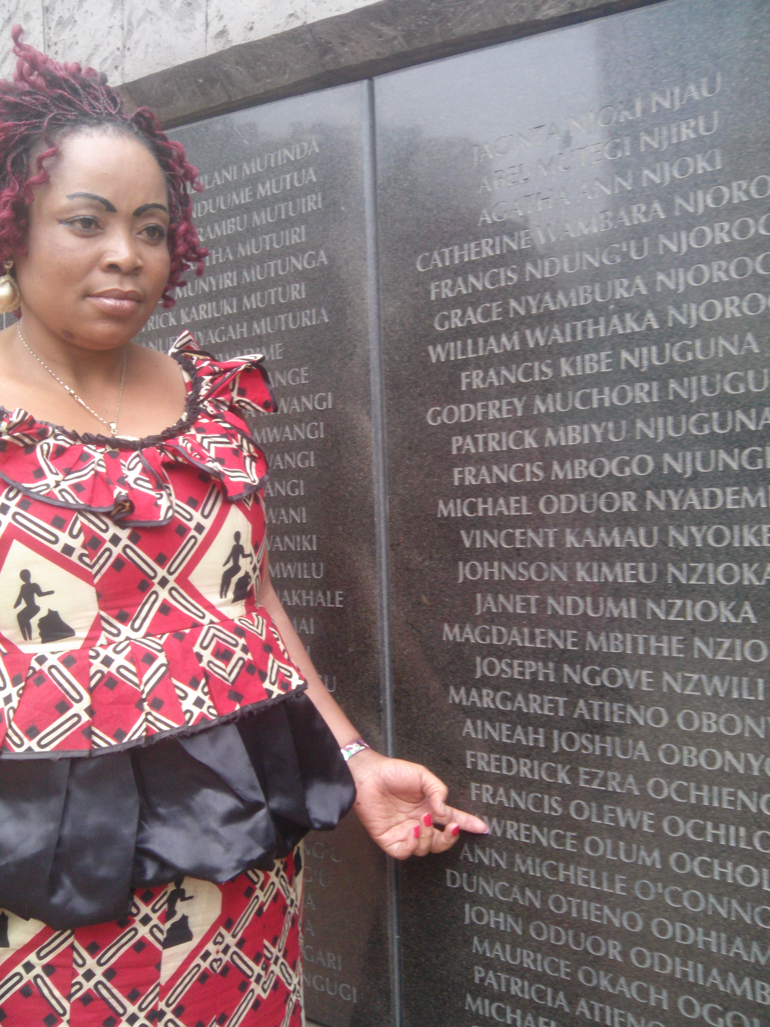 Pamela-Olum-points-at-her-late-husbands-name-at-the-1998-Bomb-blast-Memorial-Park-in-Nairobi-Her-husband-died-at-the-bomb-blast-PHOTO-BY-LILIAN-KAIVILU.jpg
