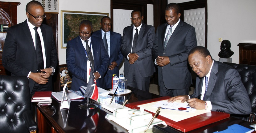 President Uhuru Kenyatta signs the 2014 Value Added Tax (VAT) and Pubilc Finance Management amendment Acts into law at State House, Nairobi. Looking on from left is Solicitor General Njee Muturi, Clerk of the National Assembly Justin Bundi, Cabinet Secretary National Treasury Henry Rotich, Majority Leader Aden Duale and Speaker of National Assembly Justin Muturi.