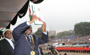 President Mwai Kibaki displays the new Kenyan constitution to the nation after he promulgated and signed it into law at a public function at Uhuru Park, Nairobi.